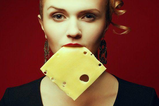 Mulher com uma fatia de queijo na boca