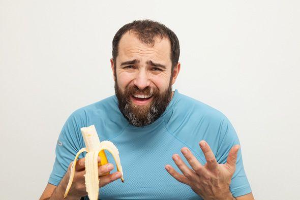 Homem infeliz sobre comer uma banana